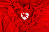 Love card with heart on a red fabric — Stock Photo