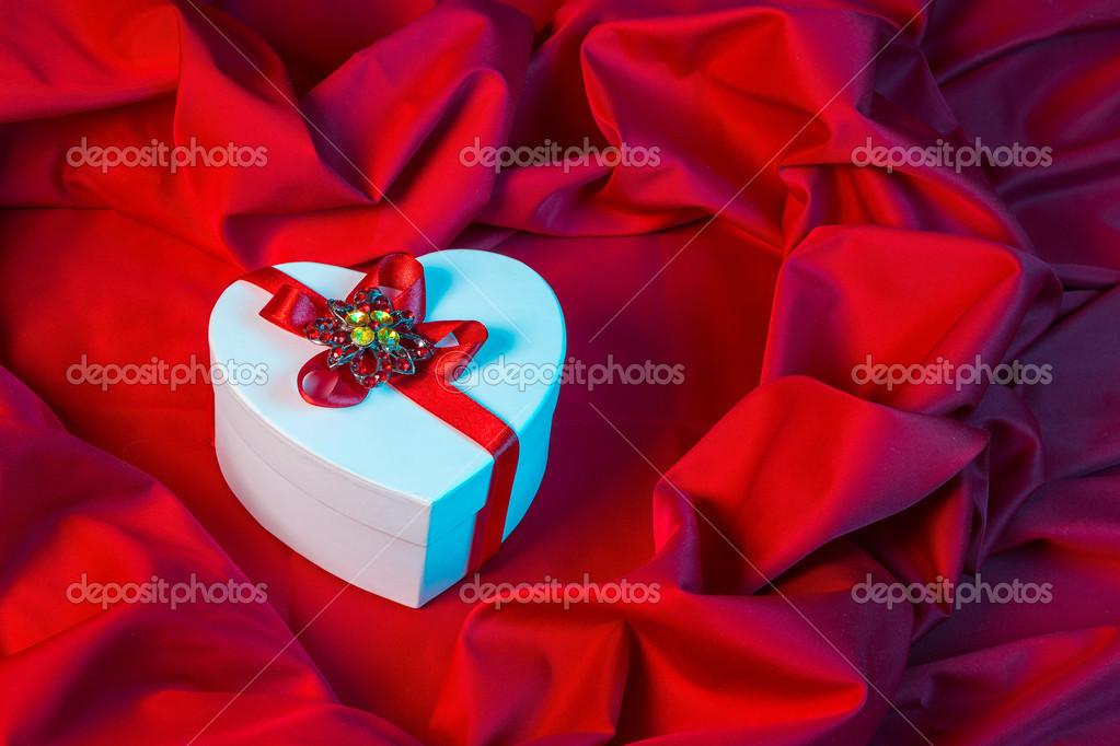 在蓝色的光的红色织物上系着红飘带的白心— photo by pellinni