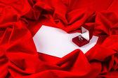 älska kort med diamantring på ett rött tyg — Stockfoto
