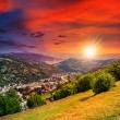 Stockfoto: Village on hillside meadow with forest in mountain at sunset