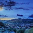 Stockfoto: Village on hillside meadow with forest in mountain at night
