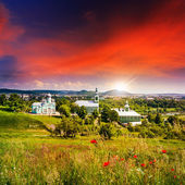 Red poppy flowers and the green monastery at sunset — Stock Photo