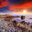 Stock Photo: Sea wave breaks about boulders at sunset