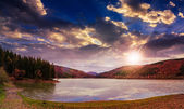 Pine forest and lake near the mountain at sunset — Stock Photo