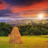 Pair of haystacks and tree at mountain at sunset — Stock Photo