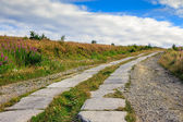 Road of concrete slabs uphill to the sky — Stock Photo