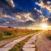 Road of concrete slabs uphill to the sunset sky — Stock Photo