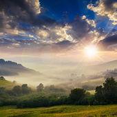 Cold fog on hot sunset in mountains — ストック写真