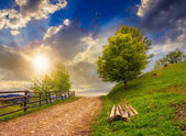 Fence on hillside meadow in mountain at sunset — Stock Photo