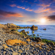 Sea wave breaks about boulders at sunset — Stock Photo #46475181