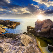 Calm sea wave touches boulders at sunset — Stock Photo