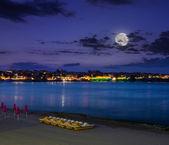 Calm sea waves on city beach at night — Foto Stock