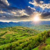 Village on hillside meadow with forest in mountain at sunset — Stock Photo