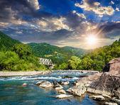 лесная река с камнями и мост на закате — Стоковое фото