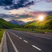Asphalt road in mountains at sunset — Foto Stock