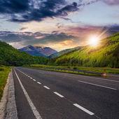 Asphalt road in mountains at sunset — Stockfoto