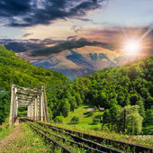 Old railroad passes in mountain village at sunset — Foto Stock