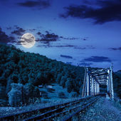 Old railroad passes in mountain village at night — Stock Photo