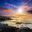 Sea wave breaks about boulders at sunset — Stock Photo #49389487