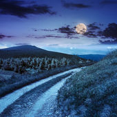 Road on a hillside near mountain peak at night — Stock Photo