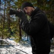 Photographer in snowy coniferous forest — Stock Photo #51473571