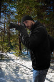 Photographer in snowy coniferous forest — Stock Photo