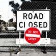Road Closed Sign Before Chain Link Fence - Stock Photo