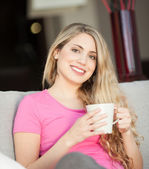 Young beautiful woman with a cup on sofa — Stock Photo