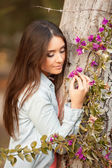 Young beautiful woman smells flowers — Stock Photo
