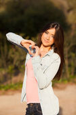 Young woman makes heart shape with hands — Stock Photo