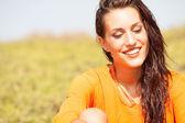Portrait of young beautiful woman laughing wearing orange shirt — Stock Photo