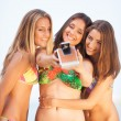 Three young beautiful girlfriends having fun on the beach with a — Stock Photo #25173949