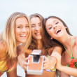 Three young beautiful girlfriends having fun on the beach with a — Stock Photo #25174441