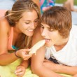 Portrait of a young beautiful couple eating melon — Stock Photo #25179149