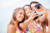 Three young beautiful girlfriends having fun on the beach with a — Stok fotoğraf