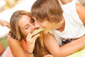 Portrait of a young beautiful couple eating melon — Stock Photo