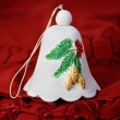 One white bell made of ceramics on a red cloth — Lizenzfreies Foto