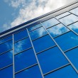 The facade of a modern building from blue glass reflects the sky — Stock Photo