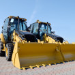 Two new bulldozers on a show-window - Stock Photo