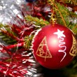 Red xmas ball hanging on fir tree — Stockfoto