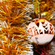 Yellow xmas ball hanging on pine twig — Stock Photo