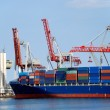 The cargo ship with containers unloads in port - Stock Photo