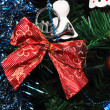 Red bow knot hanging on fir tree — Stok fotoğraf