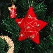 Red star hanging on fir tree — Stock Photo #12118636