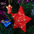 Red star hanging on fir tree — Stock Photo