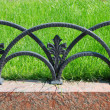 Decorative fencing near sidewalk in park - Stock Photo