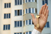 Buying new apartment. The hand holds a key highly. — Stock Photo