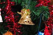 Golden bell hanging on fir tree — Stock Photo