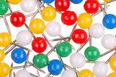 Background from color thumbtacks on white — Stock Photo