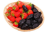 Basket with strawberry and prune on white — Stock Photo